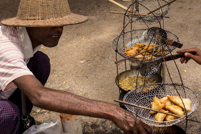 Burmese man cooking samosas at the Three Pagodas Pass border market