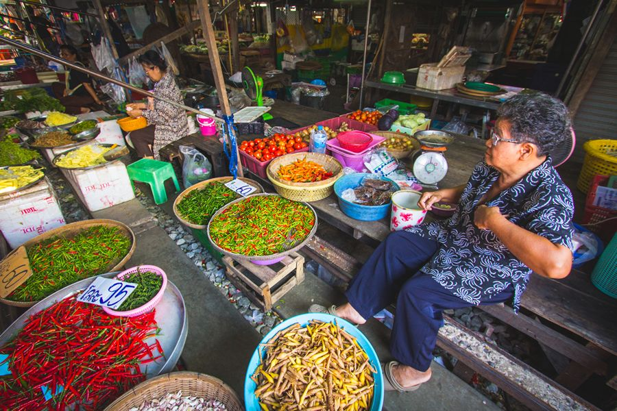 Locals selling produce at the Bangkok Train Market