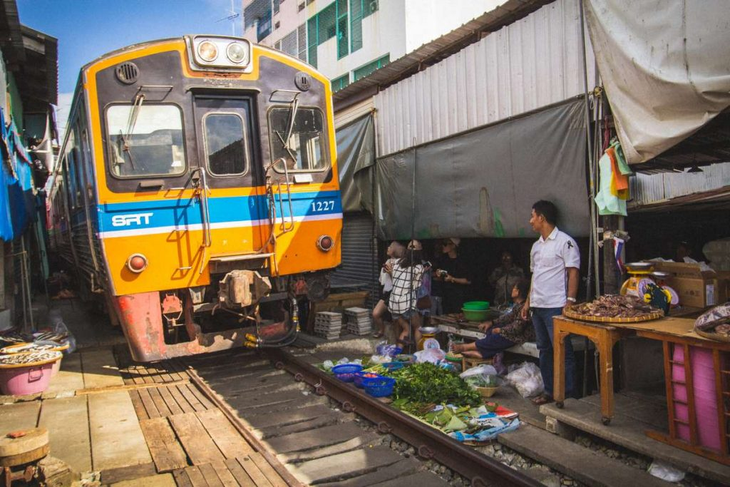 Train passing through the Maeklong Railway Market