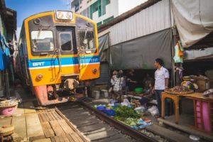 Train passing through the Maeklong Railway Market